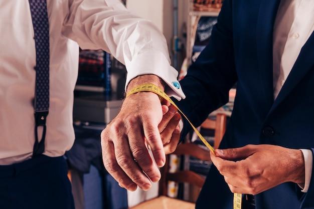 彼の顧客の手首の測定を取っているプロのファッションデザイナー