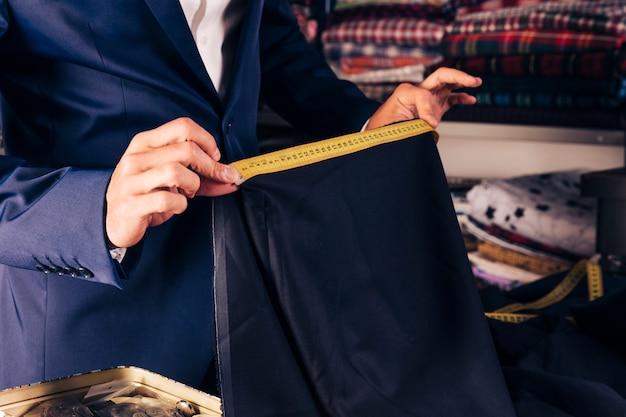 黄色の測定テープで青い布の測定を取る男性のファッション・デザイナーの手のクローズアップ