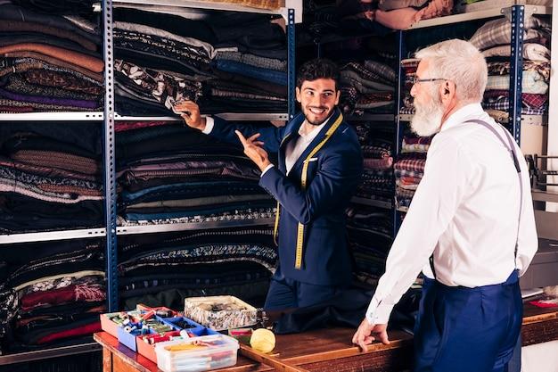 Усмехаясь портрет человека показывая ткань к его старшему мужскому клиенту в магазине