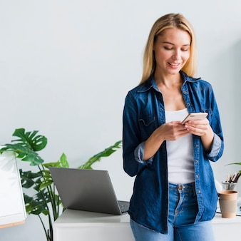 Красивая молодая женщина, используя смартфон в офисе