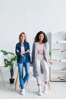 Привлекательные молодые женщины позируют в кабинете