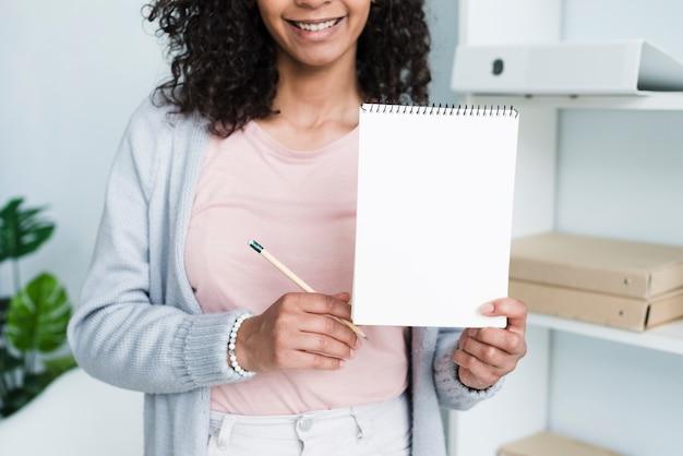 陽気な若い女性示すメモ帳