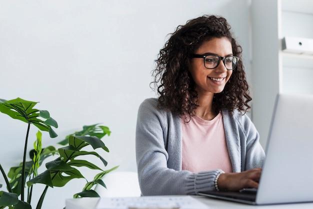 Улыбается молодая женщина, работающая на ноутбуке в офисе