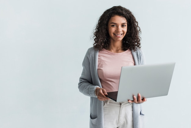 灰色のラップトップを持つ民族女性の笑みを浮かべてください。