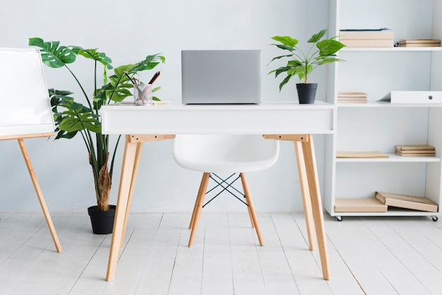Офисное рабочее место сотрудника с ноутбуком на столе
