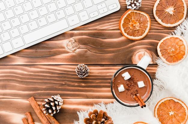 Клавиатура возле горячего шоколада, апельсинов и шишек дерева