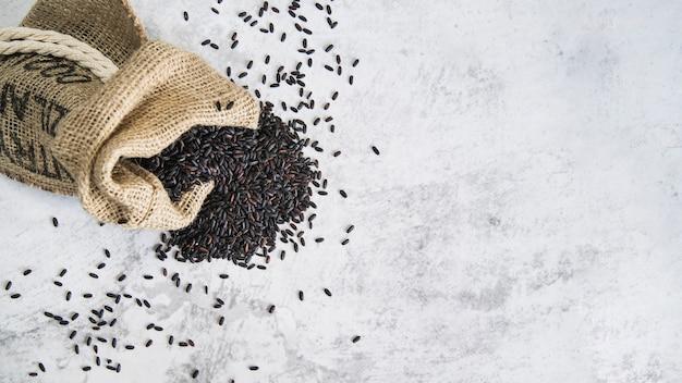 Композиция из рассыпанного черного риса в мешочке