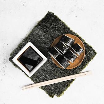 Выложите из суши роллы, палочки для еды и соус