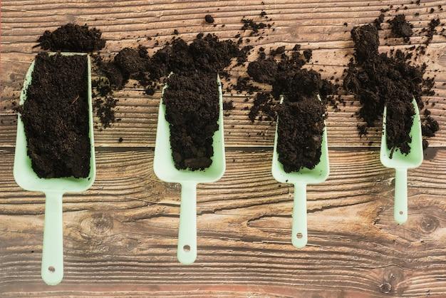 木製の机の上のサイズで配置された土と園芸ミニスクープ