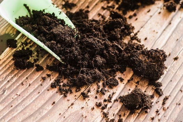 木製の机の上の暗い肥沃な土壌とプラスチックスクープ