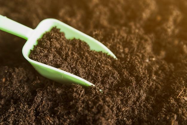 暗い土壌の中の緑色の測定スクープ