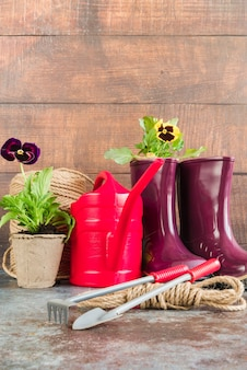 パンジー鉢植え。じょうろ;ガーデニングツール。ロープ;木製の壁に対してラバーブーツ