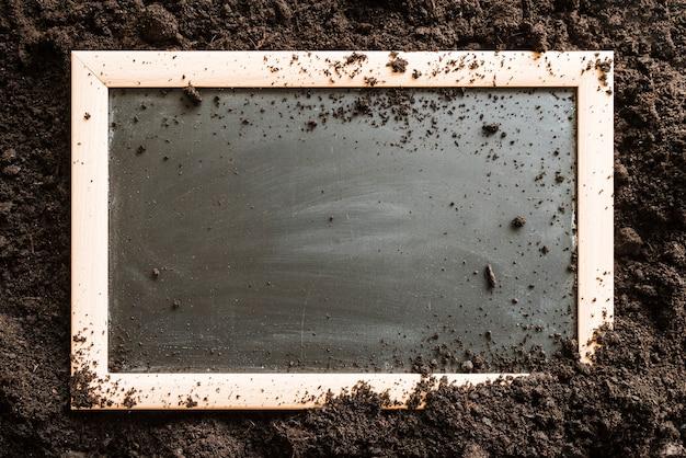 土の上の空白の木製スレート