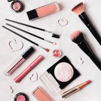 Выложите косметику для макияжа, украшенную сердечками