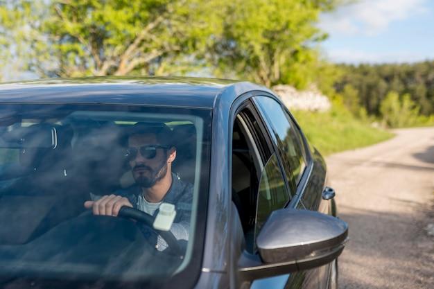 Взрослый бородатый мужчина за рулем автомобиля в солнечный день