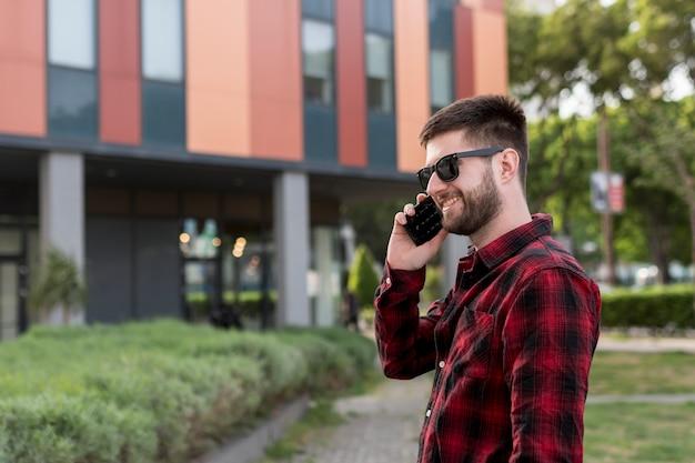 スマートフォンで話しているサングラスをかけた男性
