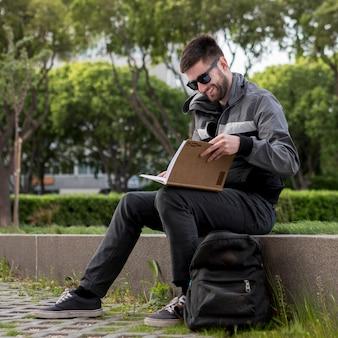 Улыбающийся человек читает книгу на улице