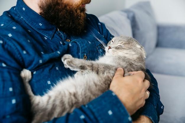 眠っている猫の手を握って男