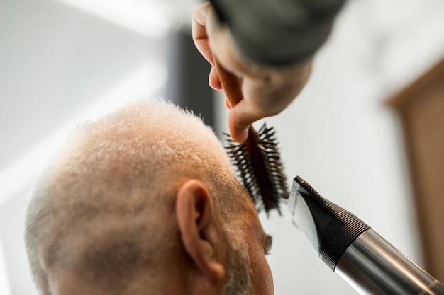 サロンで男性にスタイリングを作る美容師