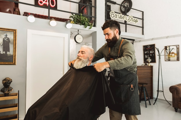 Парикмахер снимает накидку старшего клиента в парикмахерской