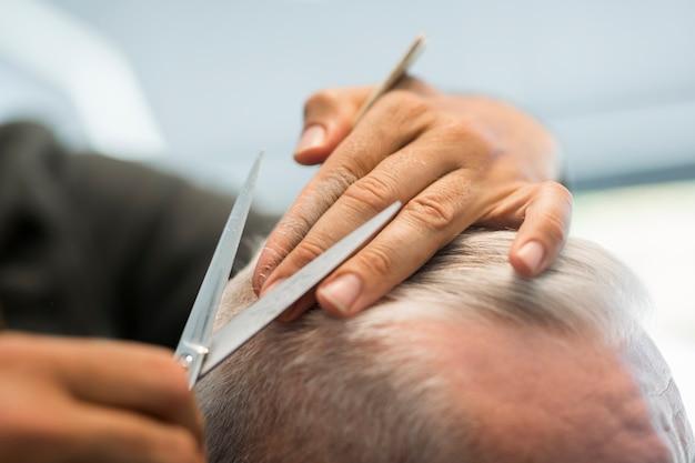 理髪店でシニアクライアントの灰色の髪をとかし、はさみ