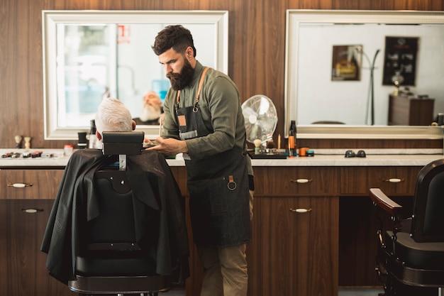 Мужской парикмахер работает с волосами пожилого клиента