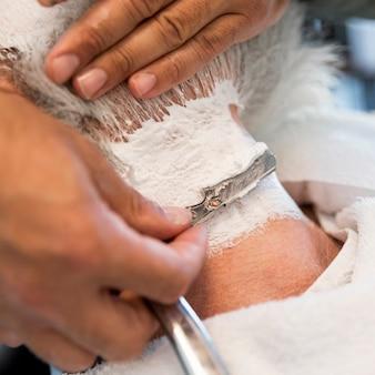 ストレートかみそりで男性の首を剃る