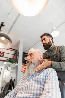 プロの理髪師が長い灰色の髭をグルーミングし終えた