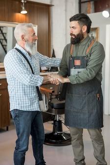 Клиент и парикмахер приветствуют друг друга в парикмахерской