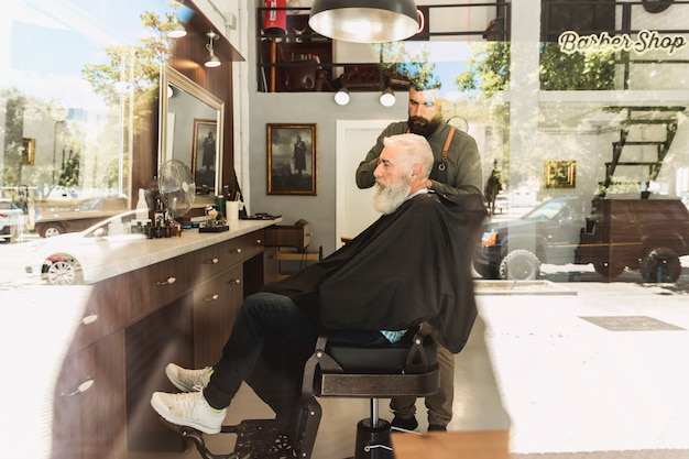 理髪店で散髪をしているひげを生やした高齢者クライアント