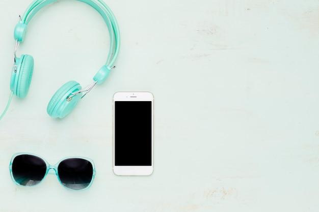 Телефон и летние аксессуары на светлом фоне