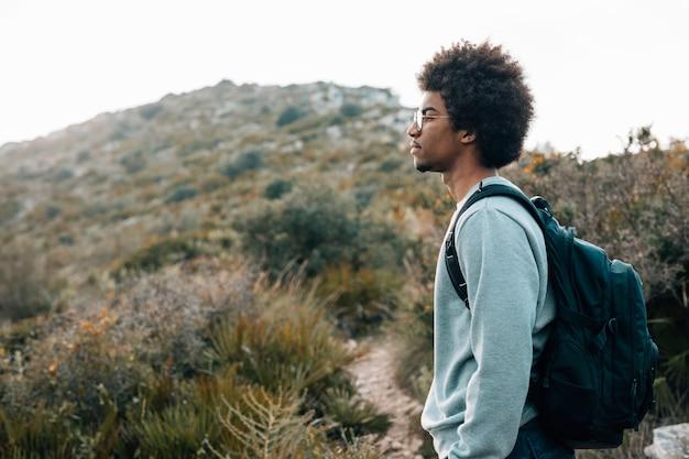 山の前に彼のバックパックに立って、アフリカの若い男のクローズアップ
