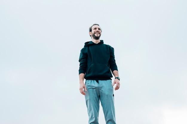 青い空を背景に立っている男の肖像を笑顔