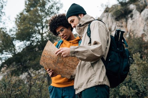 自然の中でハイキングしながら地図を読んでハイカーの低角度のビュー