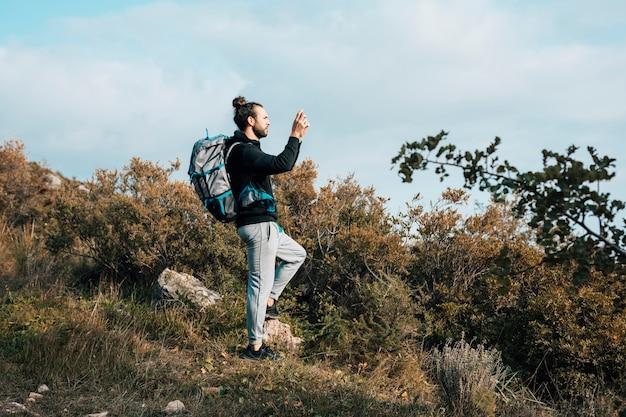 山で写真を撮る彼のバックパックを持つ男性ハイカー