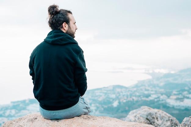 Молодой мужчина турист, сидя на вершине скалы, глядя на вид