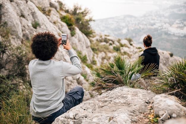 Вид сзади человека, делающего фотографию его друга, сидящего на скале с мобильным телефоном