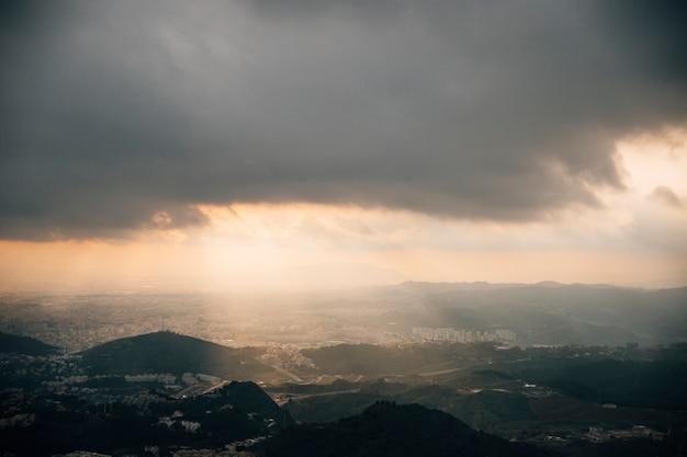 都市景観の山の上の暗い空を貫通する光のシャフト
