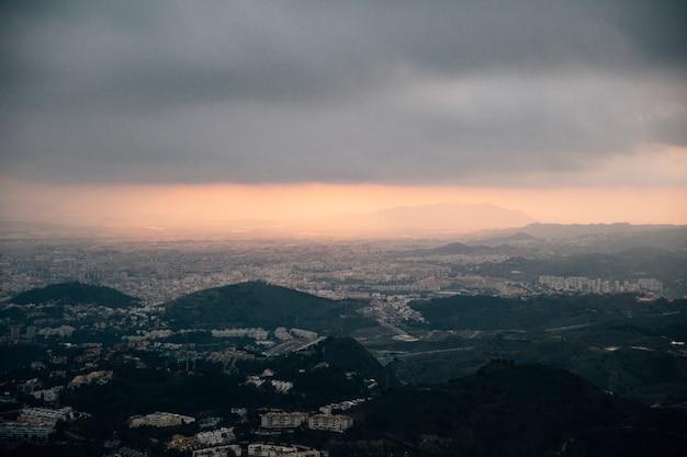 都市の景観と嵐雲の下の山