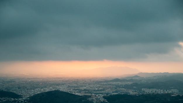 Пасмурные облака над горой и городской пейзаж