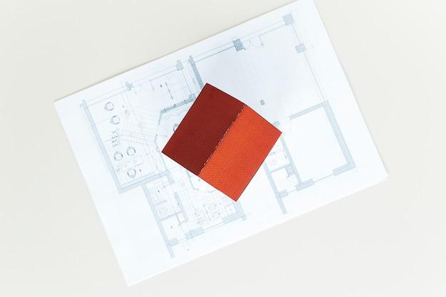 白いテーブルの上の青写真の赤い屋根の家モデルの高角度のビュー