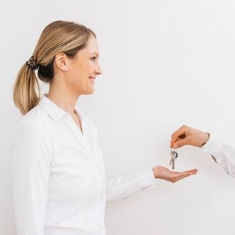 男からキーを受け取る白人女性の笑みを浮かべてください。