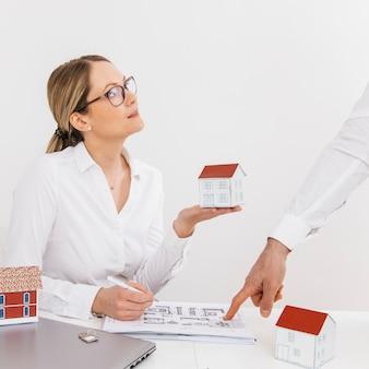 机の上の青い印刷を指している彼女の同僚を見て家モデルを保持している女性