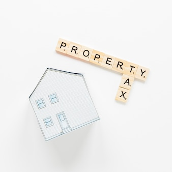 白い背景の上の財産と税のテキストを持つブロックの近くの家モデル