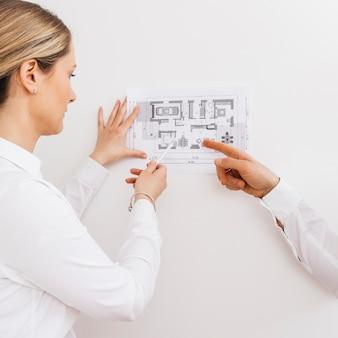 若い女性建築家およびデザイナーの新しいアパートの青写真プロジェクトに取り組んで