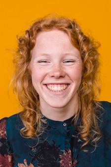 笑って生姜巻き毛の若い女性