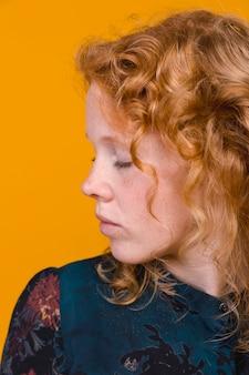 赤毛の若い女性が目を閉じて目をそらして
