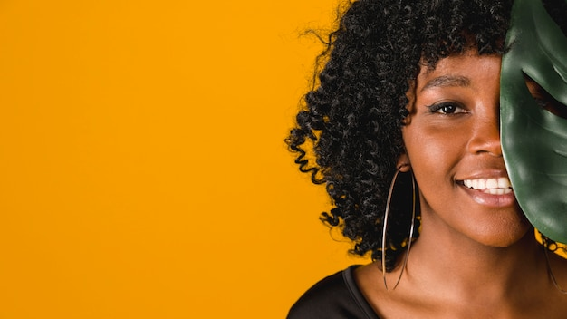 色付きの背景上の葉を持つ若いアフリカ系アメリカ人女性の笑みを浮かべてください。