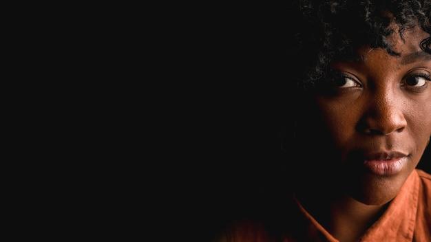 黒の背景に美しい若いアフロブルネットの女性