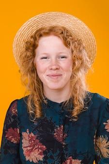 スタジオで満足している巻き毛赤毛の女性